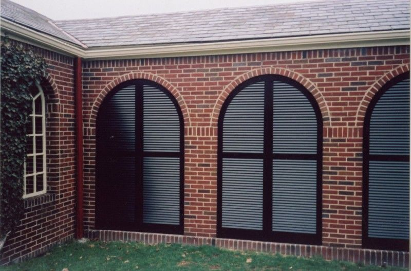 Arched Louvered Exterior Shutters enclosing a breezeway
